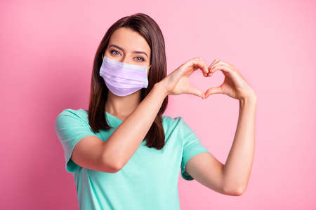 Photo portrait of girlfriend hands in heart shape in teal t-shirt respirator isolated on pastel pink color background