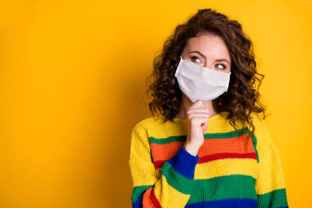Portrait of nice minded girl thinking touching chin look copy space wear mask isolated on bright yellow color background