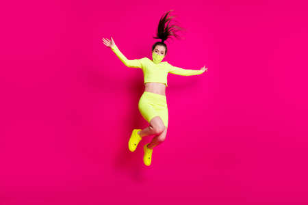 Full length body size photo of jumping high shouting energetic sporty girl laughing isolated on vibrant pink color background