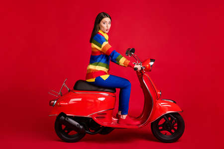 Profile side view of pretty funky flirty girl driving moped having fun pout lips isolated over bright red color background