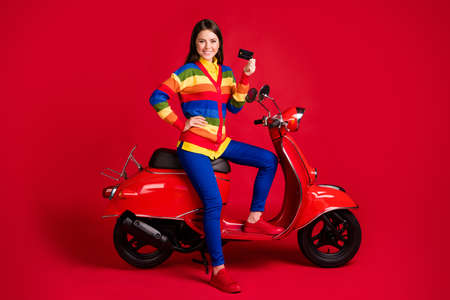 Photo portrait of confident woman holding plastic card in one hand sitting on scooter isolated on vivid red colored background