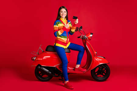 Photo portrait of woman pointing finger at credit card holding in one hand sitting on scooter isolated on vivid red colored background