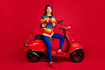 Photo portrait of excited screaming woman holding credit card in two hands sitting on scooter isolated on vivid red colored background