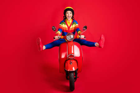 Photo portrait of excited woman spreading legs like star riding scooter isolated on vivid red colored background