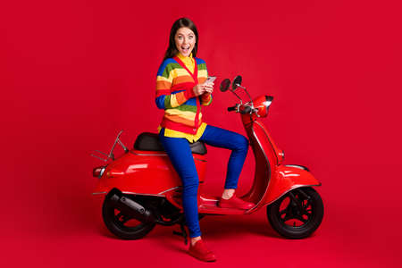 Photo portrait of excited girl holding phone in two hands sitting on scooter isolated on vivid red colored background
