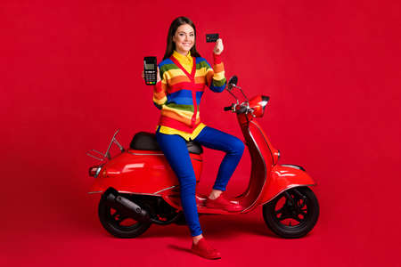 Photo portrait of happy woman holding credit card terminal in hands sitting on scooter isolated on vivid red colored background