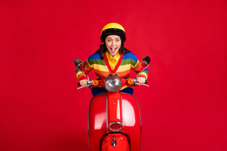 Photo portrait of screaming woman driving retro scooter really fast isolated on vivid red colored background