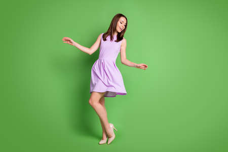 Full size photo adorable sweet careless girl lady look down hands side prom party dress air blow slim legs shoe shop advert concept wear purple dress isolated pastel green color background