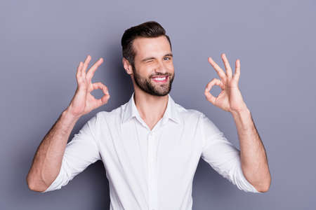 Portrait of positive cheerful confident man broker economist man approve ideal advert promotion show ok sign wink wear white shirt isolated over gray color background