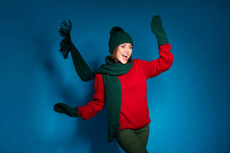Photo of crazy funky positive girl in winter warm outfit pullover pants trousers woolen mittens enjoy x-mas fairy spirit wind blow raise hands isolated over gradient blue color background