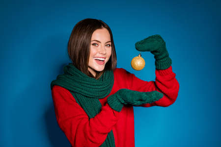 Photo of cute attractive young girl smiling hold palm presenting bauble promoting best sale proposition wear red pullover green scarf gloves isolated dark blue color background