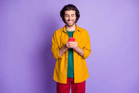 Photo of young good mood happy smiling handsome man guy male texting in smartphone isolated on purple color background