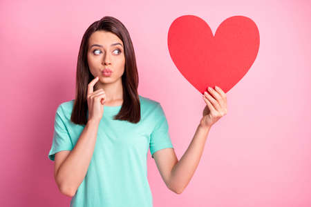 Photo portrait of cute girl sending air kiss pouted lips keeping red heart looking at copyspace isolated on pastel pink color background Reklamní fotografie