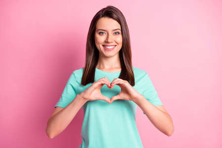 Photo portrait of romantic girl showing heart with fingers symbol of love in turquoise t-shirt isolated on pastel pink color background