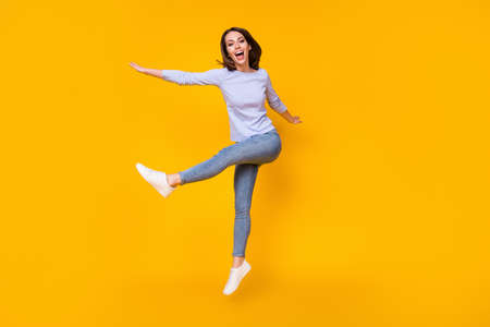Full length body size view of her she attractive pretty lovely funky cheerful cheery girl jumping having fun fooling dancing isolated bright vivid shine vibrant yellow color background