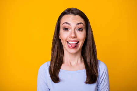 Closeup photo of attractive pretty cheerful lady good mood sticking tongue out mouth teasing boyfriend fooling around wear casual shirt isolated vibrant yellow color background