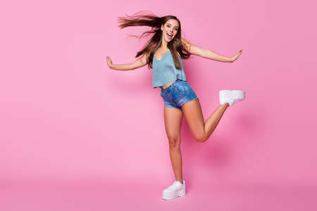 Look i cute bird. Full length photo of candid energetic funky girl enjoy spring free time weekend hold hands wear tank-top shoes isolated over pink color background