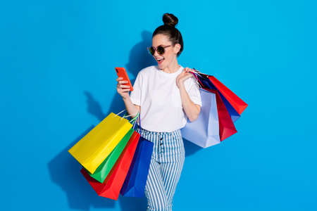 Positive cheerful girl shopping center client use smartphone read social network off-sales notification hold bags wear white t-shirt striped denim jeans isolated bright shine color background