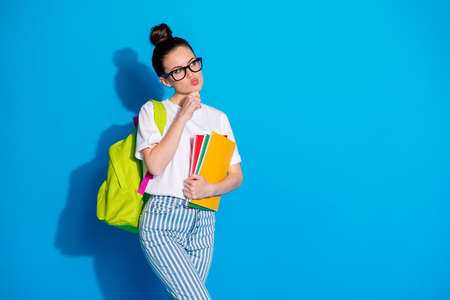 Unaware girl high school student hold backpack books copybook look copyspace think thoughts cant decide choose courses lectures wear white jeans isolated bright shine color background