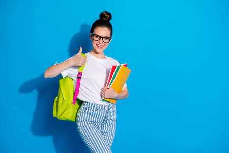 Portrait of her she nice attractive pretty cheerful cheery girl diligent nerd carrying exercise book showing thumbup excellent a-mark isolated bright vivid sine vibrant blue color background