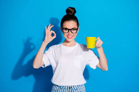 Portrait of her she nice attractive pretty cheerful cheery glad girl drinking cacao latte milk showing ok-sign symbol ad advert choose choice isolated bright vivid sine vibrant blue color background