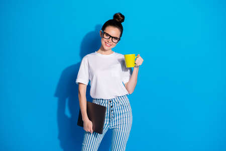 Portrait of nice attractive lovely pretty cheerful cheery girl remote manager consultant holding in hand carrying laptop drinking cacao latte isolated bright vivid sine vibrant blue color background