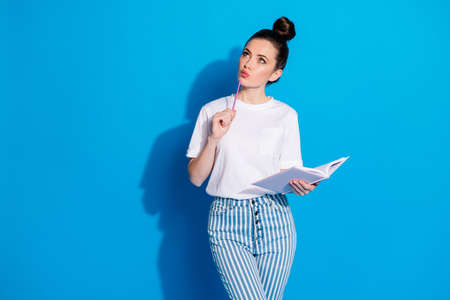 Portrait of her she nice attractive pretty lovely smart clever minded girl overthinking writing to-to list fantasizing learning poem isolated on bright vivid sine vibrant blue color background