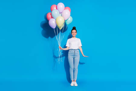 Full length body size view of nice attractive lovely charming pretty cheerful cheery girl holding in hands bunch decorative air balls isolated on bright vivid sine vibrant blue color background
