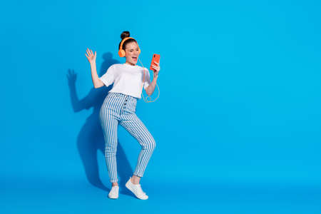 Full length body size view of her she nice attractive pretty glad cheerful cheery girl listening bass soul jazz dancing having fun weekend isolated on bright vivid sine vibrant blue color background