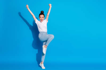 Full length body size view of her she nice attractive pretty cheerful cheery girl jumping rejoicing celebrating holiday having fun leisure isolated on bright vivid sine vibrant blue color background