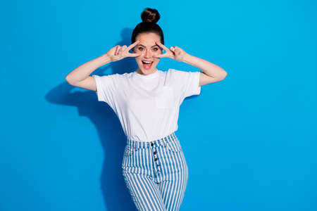 Portrait of her she nice attractive lovely pretty positive glad cheerful cheery girl showing double v-sign having fun isolated over bright vivid sine vibrant blue color background