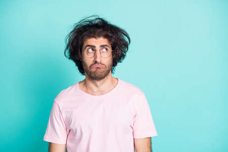 Portrait of sad uncombed hairdo man looking empty space wear spectacles pastel pink t-shirt isolated on teal color background