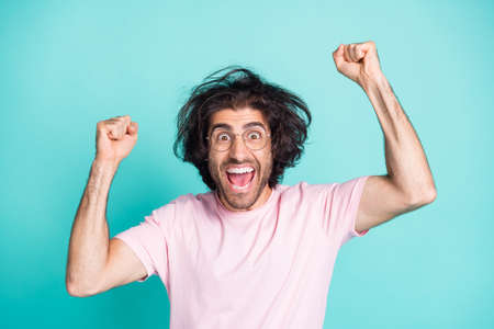 Portrait of hooray cheerful uncombed hairdo man hands fists yell wear spectacles pastel pink t-shirt isolated on teal color background
