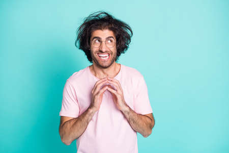 Portrait of crazy genius uncombed hairdo guy arms together look empty space wear spectacles pastel pink t-shirt isolated on teal background