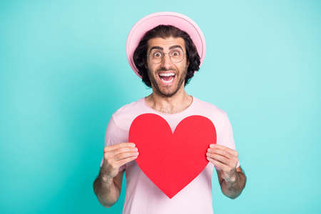 Portrait of optimistic funny guy showing paper heart wear pink cap t-shirt spectacles isolated on teal color background