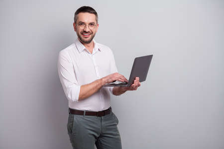 Portrait of nice attractive cheerful cheery successful mature man holding in hands laptop creating web design presentation isolated over light gray pastel color background
