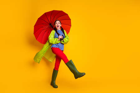 Full length body size view of her she nice attractive pretty funky cheerful girl wearing green coat gums parasol having fun going isolated bright vivid shine vibrant yellow color background