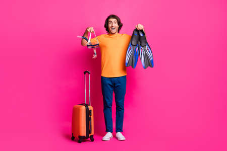Full length photo of guy luggage show mask flips open mouth wear orange t-shirt jeans sneakers isolated pink color background