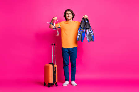 Full length photo of man baggage hold mask flips wear orange t-shirt jeans sneakers isolated pink color background