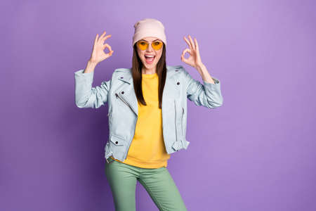 Portrait of crazy energetic girl enjoy excellent promo ads recommend choose decide show okay sign wear yellow green pants isolated over purple color background