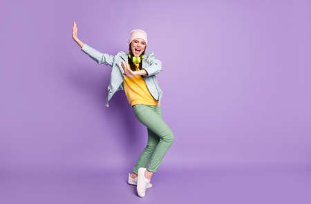 Full body photo of cool funky attractive lady street clothes good mood dancing youngster moves raise hands wear casual hat jacket pants shoes isolated purple color background Stock Photo