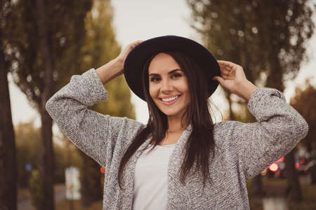 Photo portrait of beautiful brunette woman relaxing in city streets on weekend smiling in fall evening wearing stylish outfit