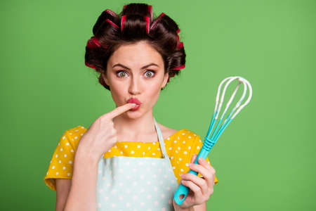 Photo of lovely cute young girl roller hairdo lips lick finger tasting dough bake biscuit hold plastic whisk staring shocked wear dotted apron shirt isolated green color background
