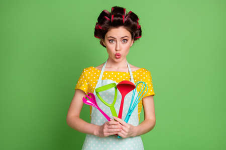 Photo of cute girl hold kitchen equipment whisk spoon fork spatula potato masher make her lips pouted wear yellow dotted t-shirt isolated over green color background Stock fotó