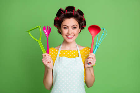 Photo of positive girl hold spatula spoon fork potato masher whisk enjoy kitchen equipment wear good look clothes isolated over green color background