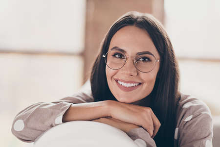 Portrait of pretty optimistic girl hands face wear spectacles pijama at home Foto de archivo