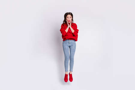 Full length body size photo of jumping female student amazed keeping hands on cheeks opened mouth isolated on grey pastel color background Фото со стока
