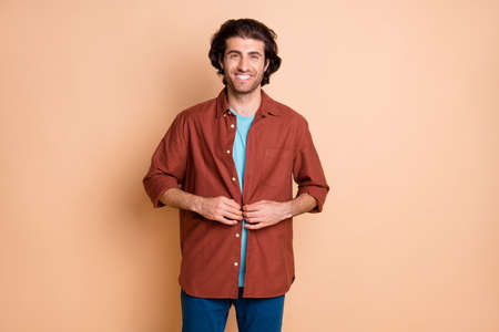 Photo of smiling cute young man wear casual brown outfit fasten shirt button isolated beige color background