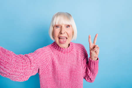 Photo portrait of excited elderly woman showing v-sign taking selfie isolated on pastel blue colored background Foto de archivo