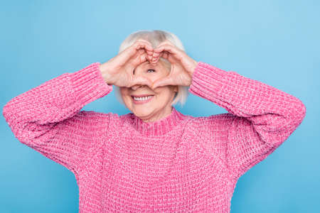 Photo portrait of old lady making heart shape with fingers on one eye looking through it isolated on pastel blue colored background Stockfoto